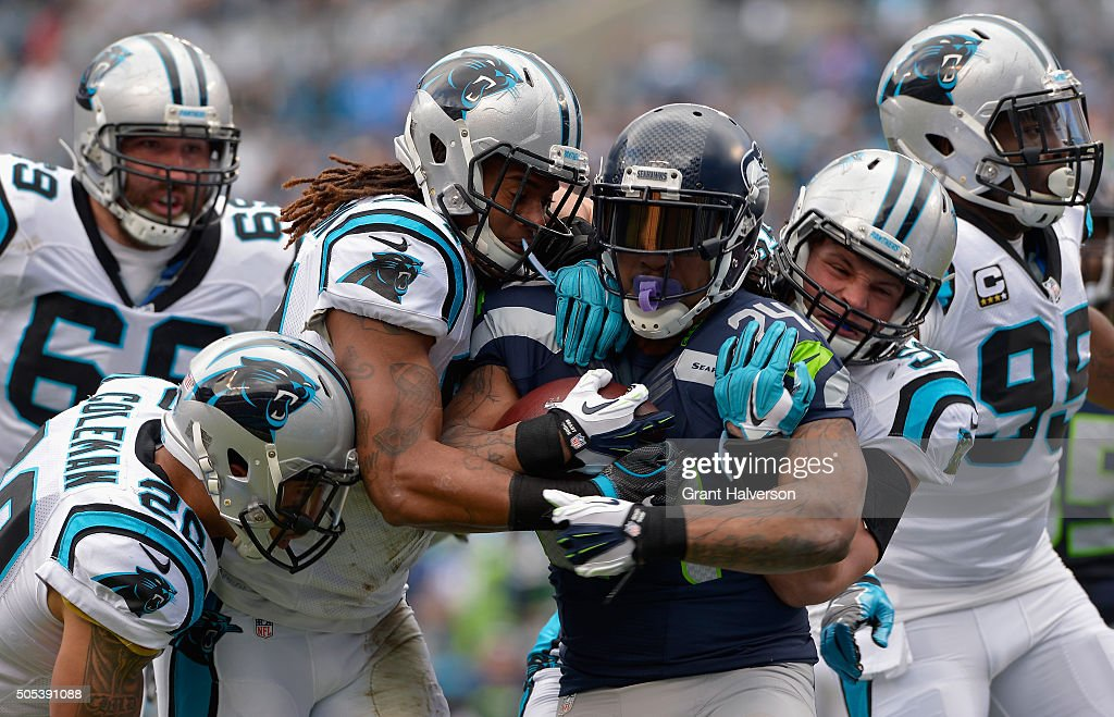 Luke Kuechly and Shaq GreenThompson of the Carolina Panthers attempt to tackle Marshawn Lynch of the Seattle Seahawks during the NFC Divisional...