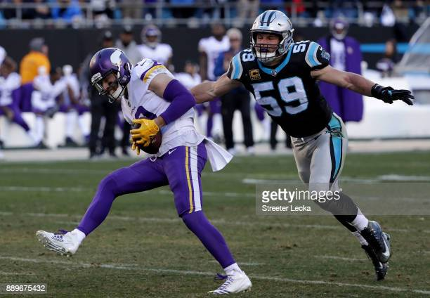 Luke Kuechly of the Carolina Panthers tackles Adam Thielen of the Minnesota Vikings in the third quarter during their game at Bank of America Stadium...