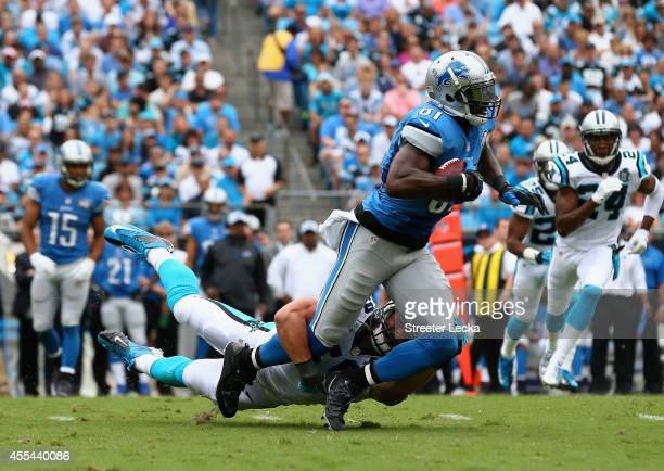 Luke Kuechly of the Carolina Panthers tackles Calvin Johnson of the Detroit Lions during the game at Bank of America Stadium on September 14 2014 in...