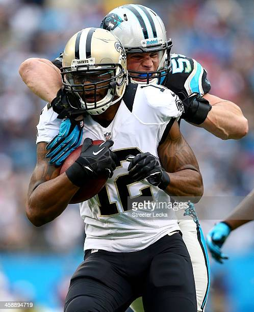 Luke Kuechly of the Carolina Panthers tackles Marques Colston of the New Orleans Saints during their game at Bank of America Stadium on December 22...