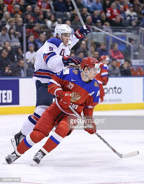 Luke Kunin of Team USA bumps into Danila Kvartalnov of Team Russia during a preliminary game at the 2017 IIHF World Junior Hockey Championship at the...