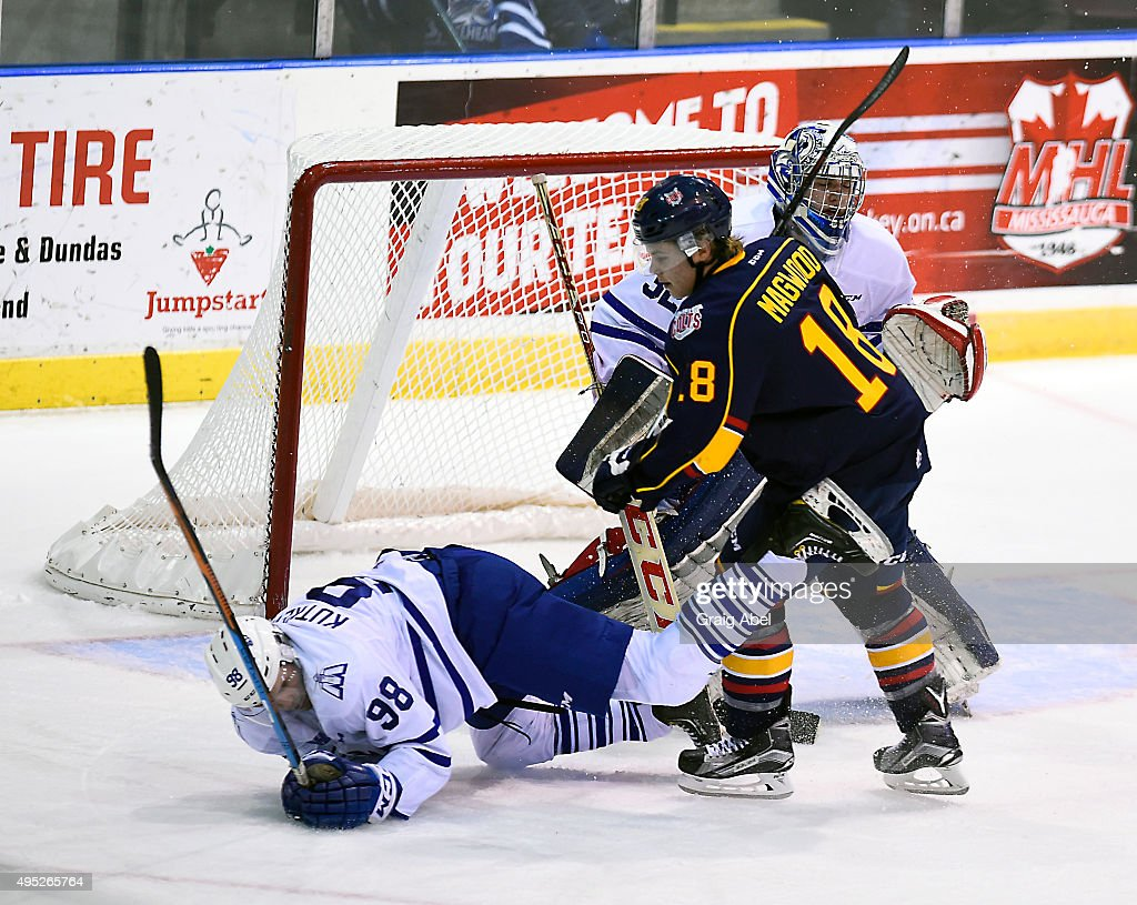 Luke Kutkevicius #98 of the Mississauga Steelheads is tripped up by Zachary Magwood #18 of the Barrie Colts during OHL game action on November 1, 2015 at the Hershey Centre in Mississauga, Ontario, Canada.