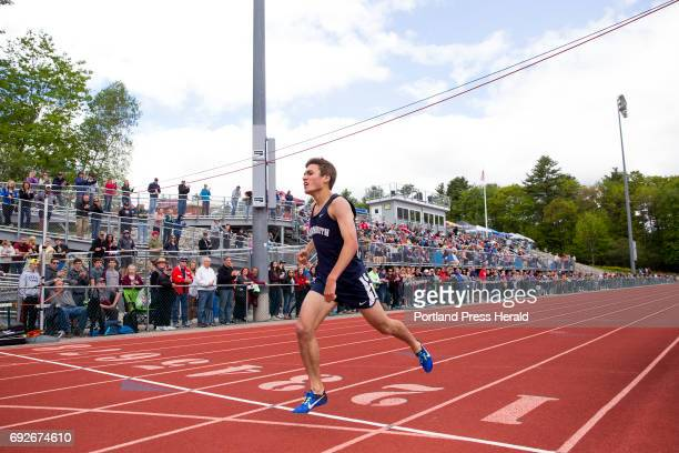 Luke Laverdiere a junior at Yarmouth runs over the finish line during the 1600 at the Class B State Track Meet at Yarmouth High School