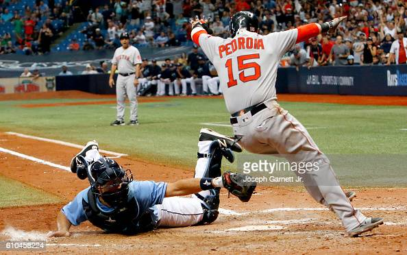 Luke Maile of the Tampa Bay Rays tries to make the tag on Dustin Pedroia of the Boston Red Sox at home plate as Pedroia scores the winning run in the...