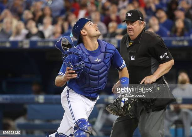Luke Maile of the Toronto Blue Jays goes after a foul ball as home plate umpire Joe West looks on during MLB game action against the Texas Rangers at...