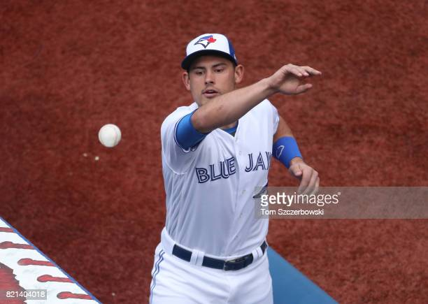Luke Maile of the Toronto Blue Jays throws a souvenir baseball to a fan during MLB game action against the Baltimore Orioles at Rogers Centre on June...