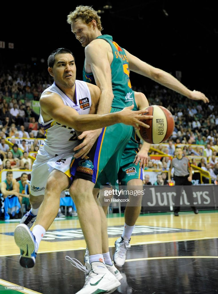 Luke Martin of the Kings passes the ball around Luke Schenscher of the Crocodiles during the round 15 NBL match between the Townsville Crocodiles and...