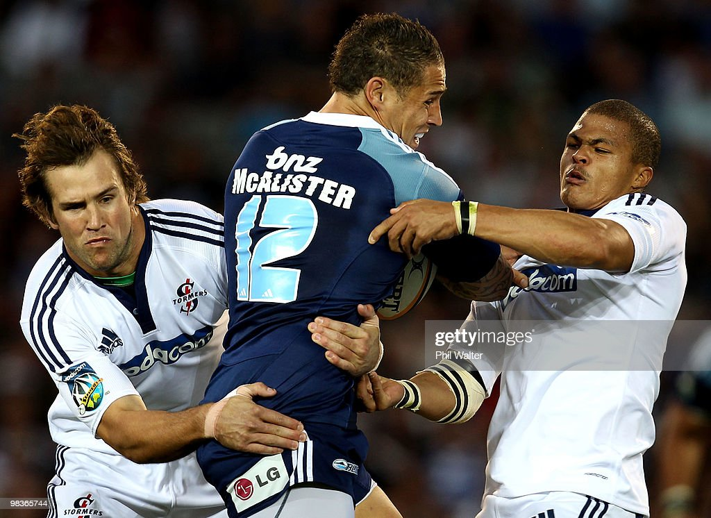 Luke McAlister of the Blues is tackled by Peter Grant (L) and Juan de Jongh (R) of the Stomers during the round nine Super 14 match between the Blues and the Stormers at Eden Park on April 10, 2010 in Auckland, New Zealand.