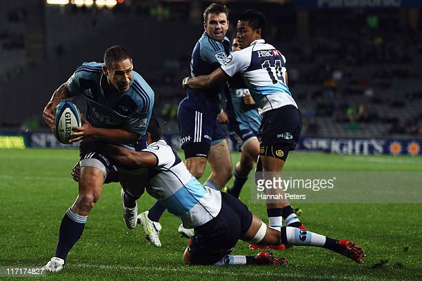 Luke McAlister of the Blues looks to offload the ball during the Super Rugby qualifier match between the Blues and the Waratahs at Eden Park on June...