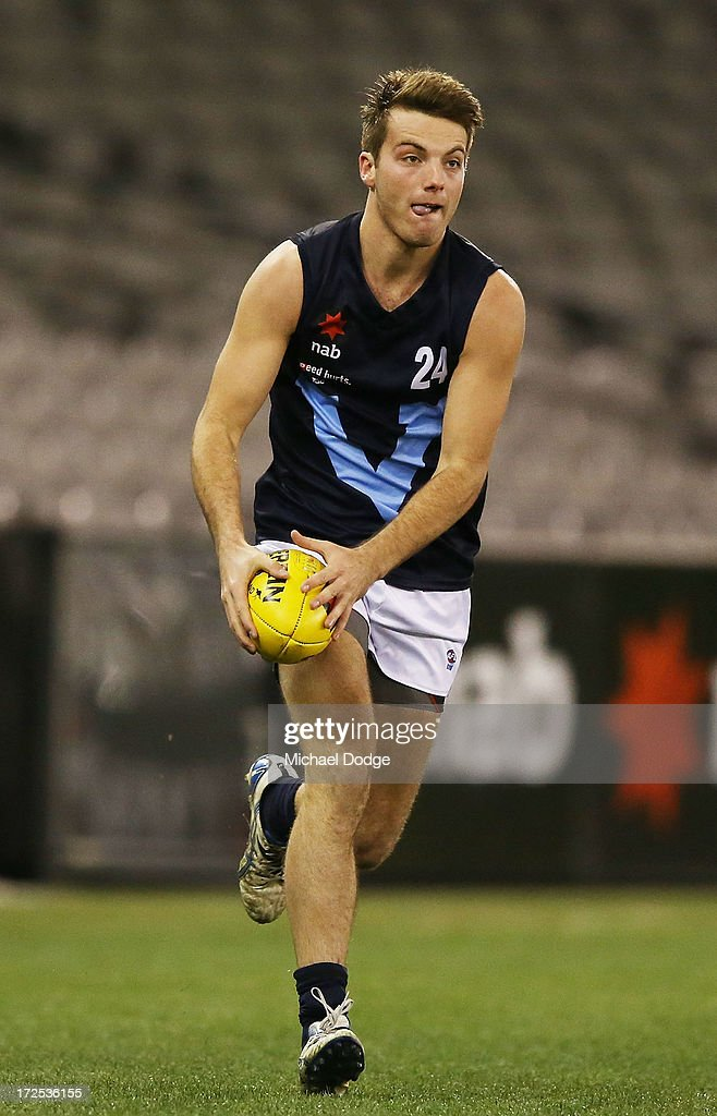 Luke McDonald of Vic Metro runs with the ball during the AFL Under 18s Championship match between Victoria Country and Victoria Metro at Etihad Stadium on July 3, 2013 in Melbourne, Australia.