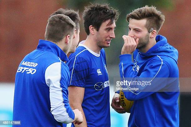 Luke McDonald whispers to Sam Wright during a North Melbourne Kangaroos training session at Aegis Park on August 25 2015 in Melbourne Australia