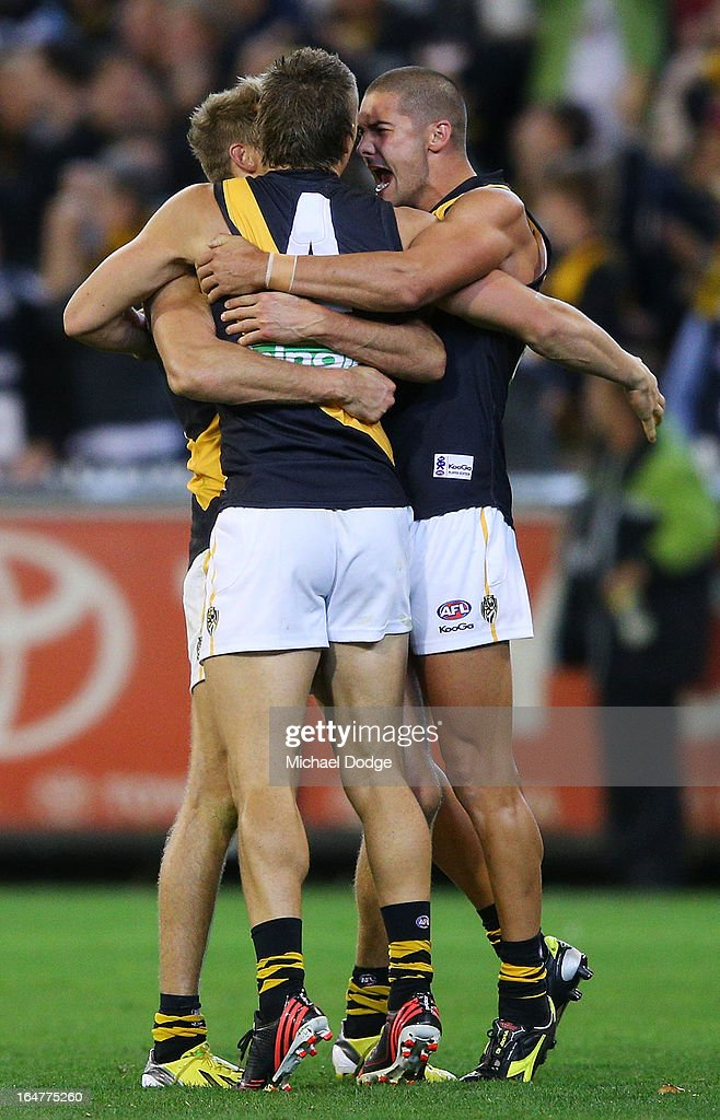 Luke McGuane (L) Dustin Martin (C) and Shaun Grigg of the Tigers celebrate their win on the final siren during the round one AFL match between the Carlton Blues and the Richmond Tigers at Melbourne Cricket Ground on March 28, 2013 in Melbourne, Australia.
