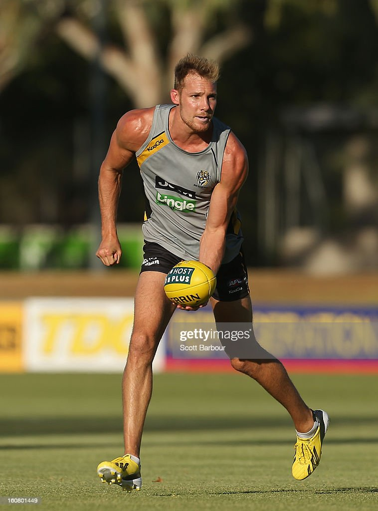 Luke McGuane of the Tigers passes the ball during a Richmond Tigers AFL training session ahead of the AFL exhibition match between the Richmond Tigers and the Indigenous All Stars at Traeger Park on February 6, 2013 in Alice Springs, Australia.