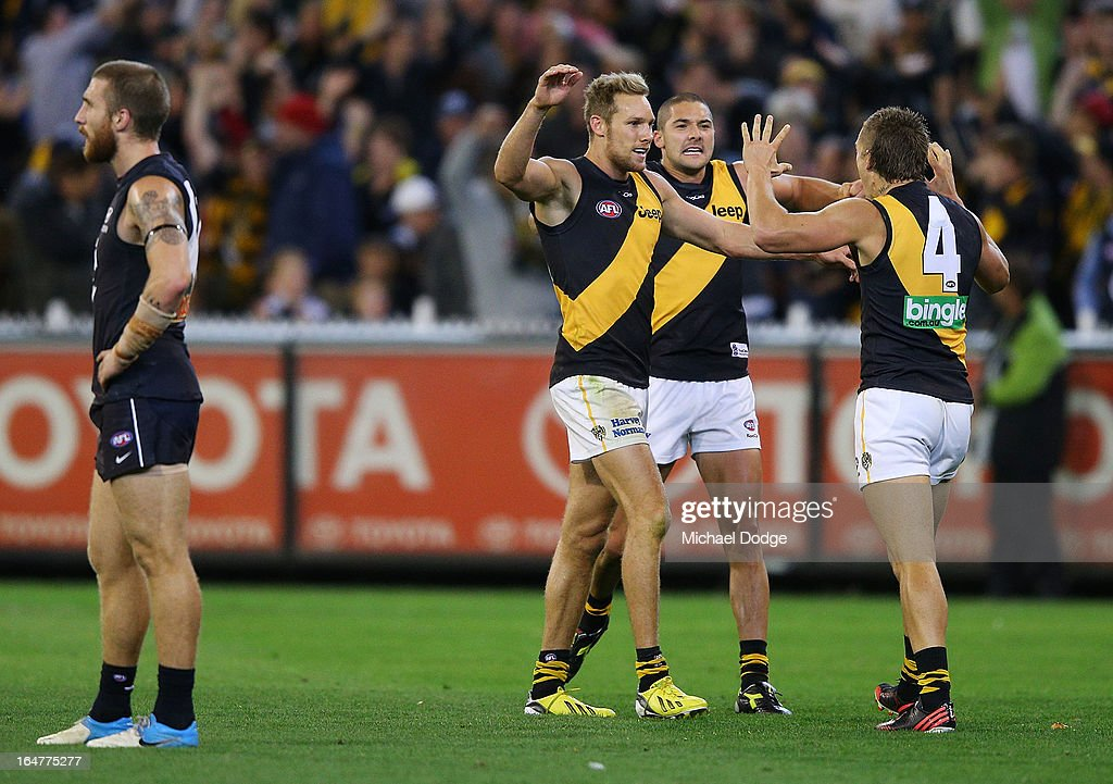 Luke McGuane, Shaun Grigg and Dustin Martin (R) of the Tigers celebrate their win on the final siren next to Zac Tuohy (L) of the Blues during the round one AFL match between the Carlton Blues and the Richmond Tigers at Melbourne Cricket Ground on March 28, 2013 in Melbourne, Australia.
