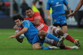 Luke Mclean of Italy is tackled by Siviteni Mafi of Tonga during the international test match between Italy and Tonga at Mario Rigamonti Stadium on...
