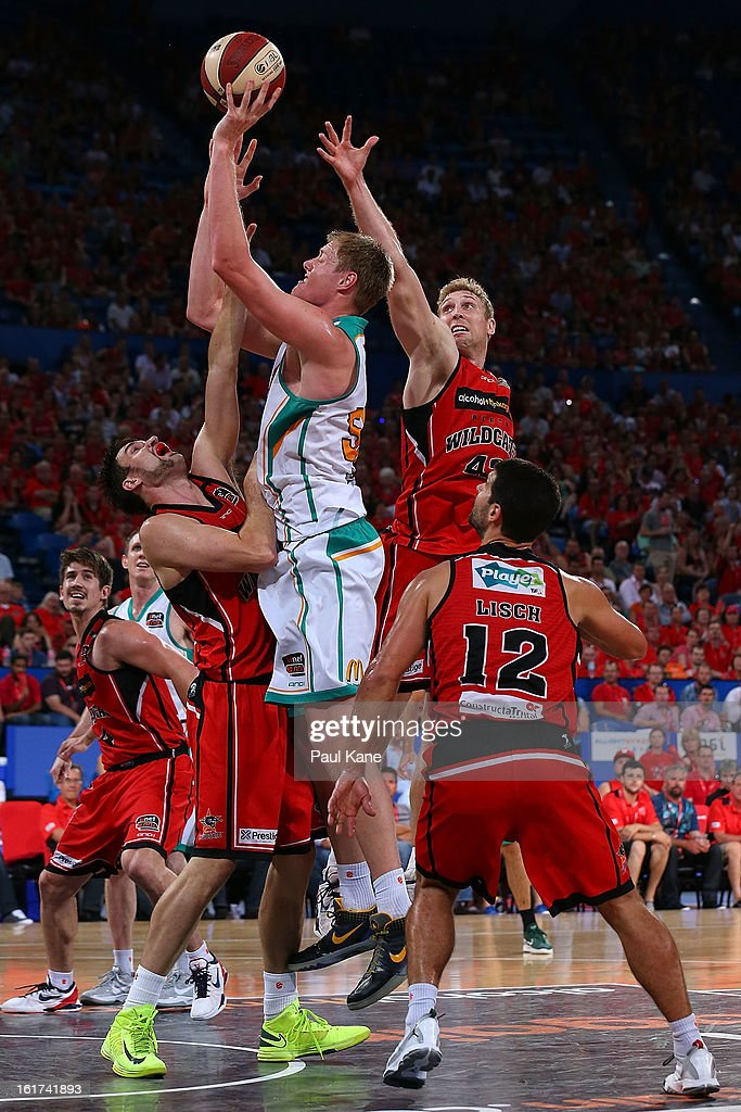 Luke Nevill of the Crocodiles takes a shot against Jeremiah Trueman and Shawn Redhage of the Wildcats during the round 19 NBL match between the Perth Wildcats and the Townsville Crocodiles at Perth Arena on February 15, 2013 in Perth, Australia.
