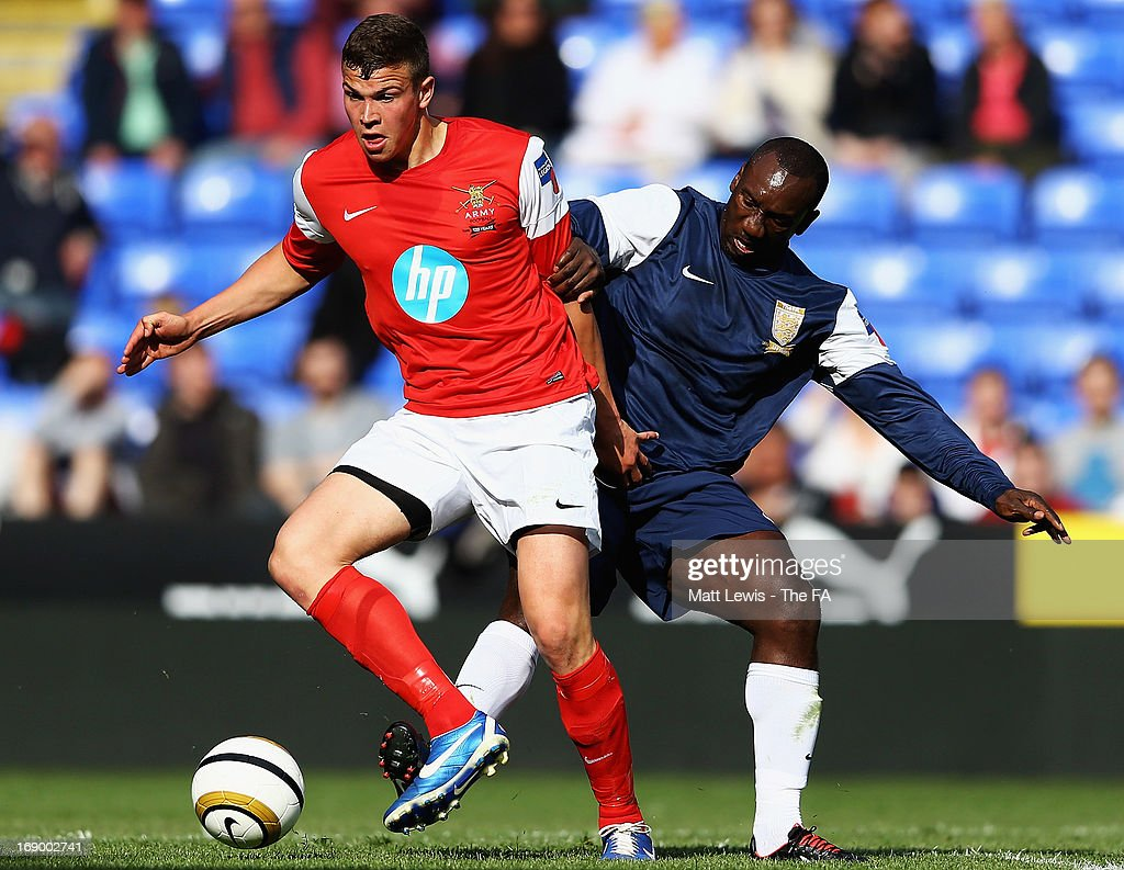 Luke Noble of the Army FA tackles <a gi-track='captionPersonalityLinkClicked' href=/galleries/search?phrase=Jimmy+Floyd+Hasselbaink&family=editorial&specificpeople=209151 ng-click='$event.stopPropagation()'>Jimmy Floyd Hasselbaink</a> of the FA Legends during the Army FA and FA Legends Match at Madejski Stadium on May 18, 2013 in Reading, England.