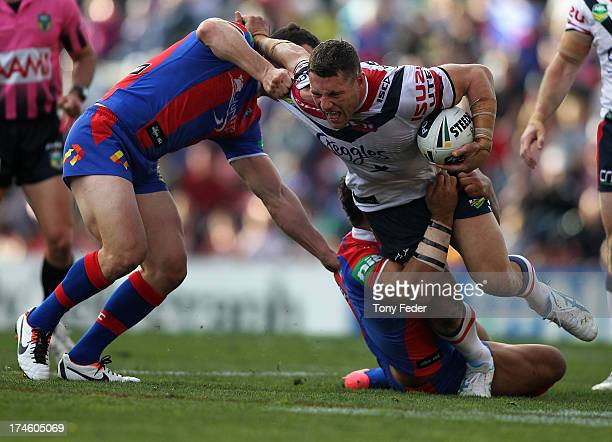 Luke O'Donnell of the Roosters attempts to break through the Knights defence during the round 20 NRL match between the Newcastle Knights and the...