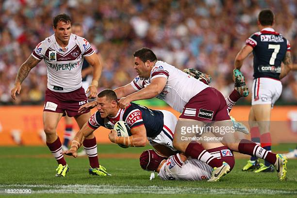 Luke O'Donnell of the Roosters is tackled during the 2013 NRL Grand Final match between the Sydney Roosters and the Manly Warringah Sea Eagles at ANZ...