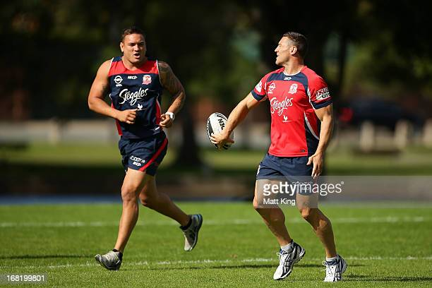 Luke O'Donnell passes to Jared WaereaHargreaves during a Sydney Roosters NRL training session at Kippax Lake on May 7 2013 in Sydney Australia