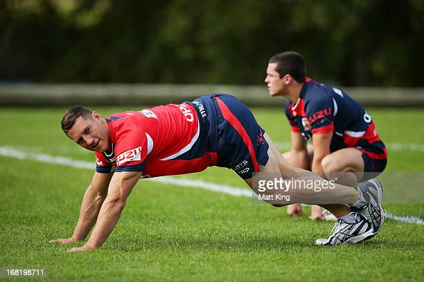 Luke O'Donnell stretches as Daniel Mortimer looks on during a Sydney Roosters NRL training session at Kippax Lake on May 7 2013 in Sydney Australia