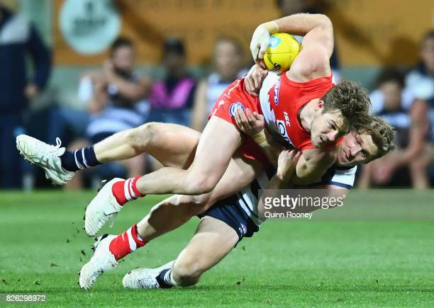 Luke Parker of the Swans is tackled by Scott Selwood of the Cats during the round 22 AFL match between the Geelong Cats and the Sydney Swans at...