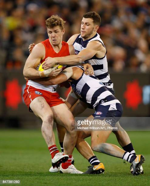 Luke Parker of the Swans is tackled by Steven Motlop and Sam Menegola of the Cats during the 2017 AFL Second Semi Final match between the Geelong...