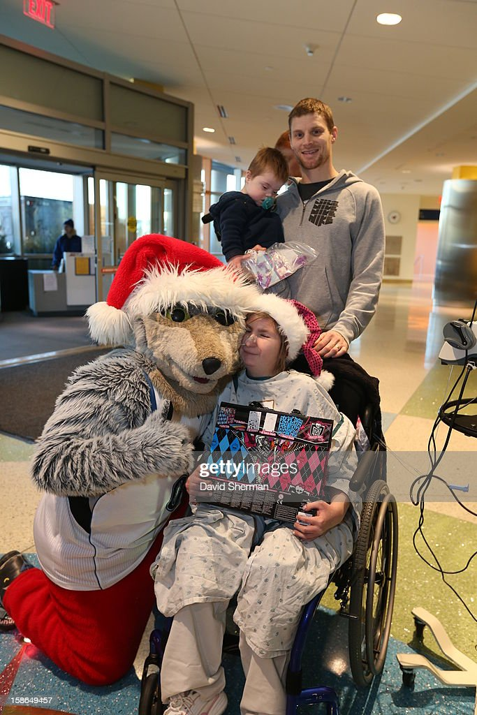 Luke Ridnour and mascot Crunch of the Minnesota Timberwolves pause from distributing holiday gifts collected through the Minnesota Timberwolves Fastbreak Foundation Toy Drive to patients and families for a photograph on December 21, 2012 at the University of Minnesota Amplatz Children's Hospital in Minneapolis, Minnesota.