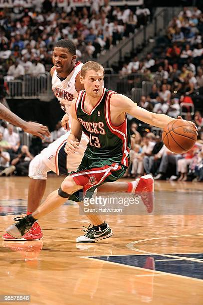 Luke Ridnour of the Milwaukee Bucks dribbles against Joe Johnson of the Atlanta Hawks in Game One of the Eastern Conference Quarterfinals during the...