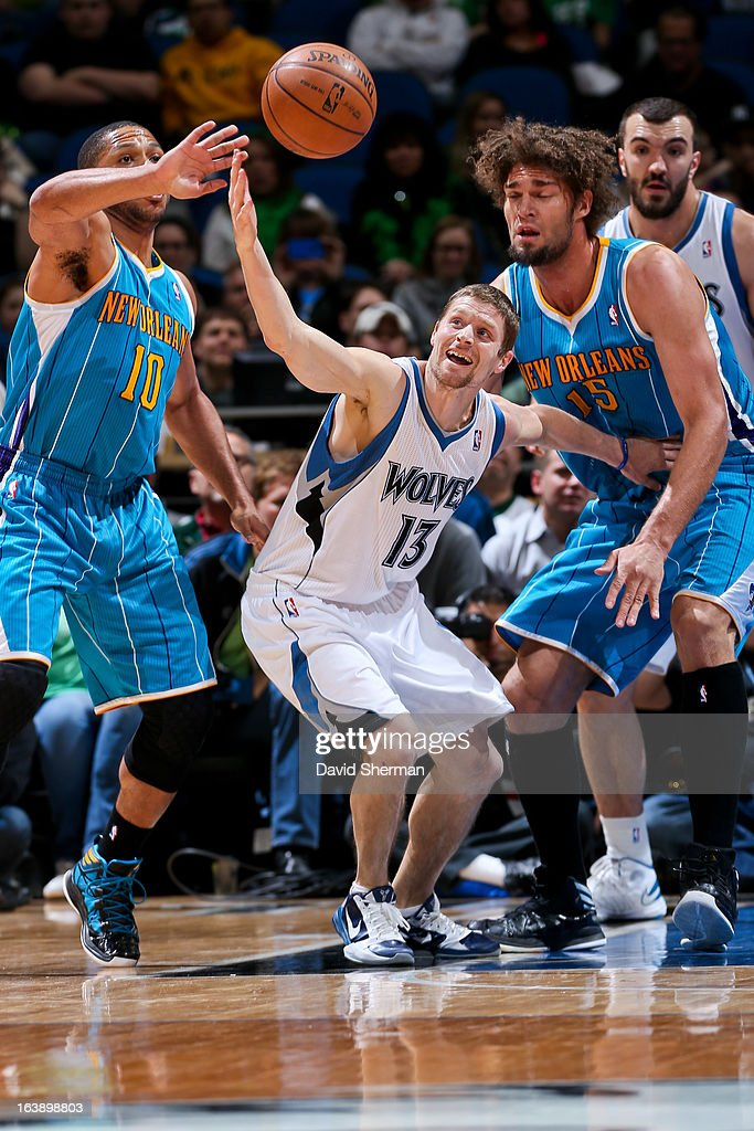 Luke Ridnour #13 of the Minnesota Timberwolves and Eric Gordon #10 of the New Orleans Hornets chase after a loose ball during their game on March 17, 2013 at Target Center in Minneapolis, Minnesota.