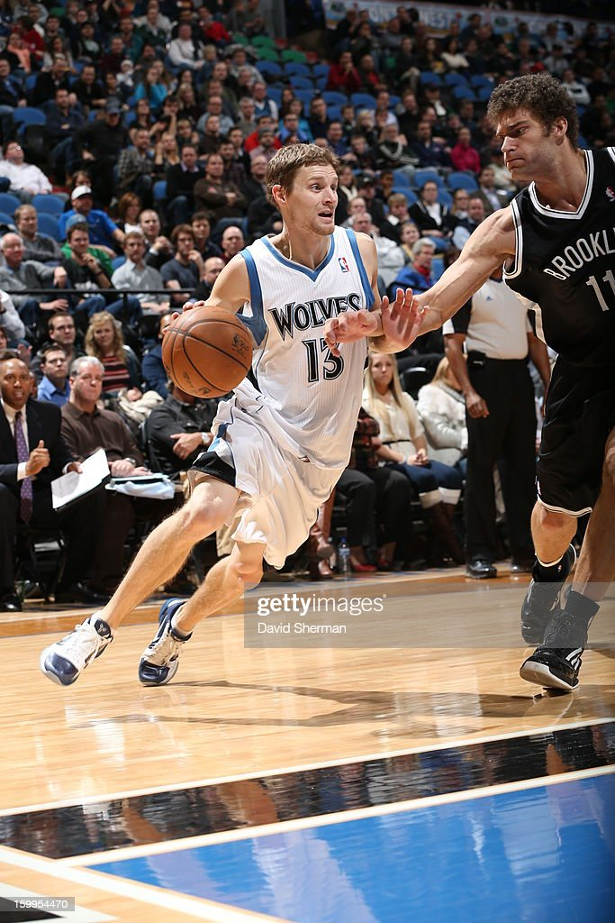 Luke Ridnour #13 of the Minnesota Timberwolves protects the ball against Brook Lopez #11 of the Brooklyn Nets during the game between the Minnesota Timberwolves and the Brooklyn Nets on January 23, 2013 at Target Center in Minneapolis, Minnesota.