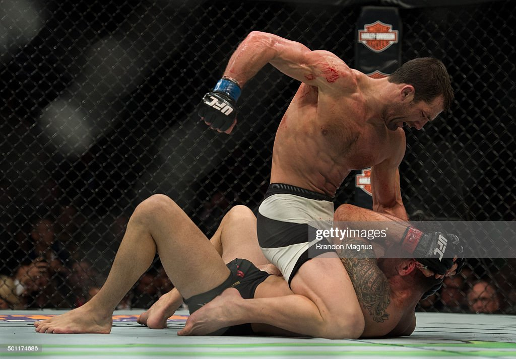 Luke Rockhold (top) punches Chris Weidman in their middleweight title fight during the UFC 194 event inside MGM Grand Garden Arena on December 12, 2015 in Las Vegas, Nevada.