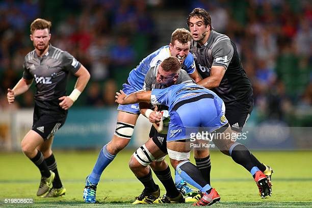 Luke Romano of the Crusaders gets tackled by Angus Cottrell and Tetera Faulkner of the Force during the round seven Super Rugby match between the...