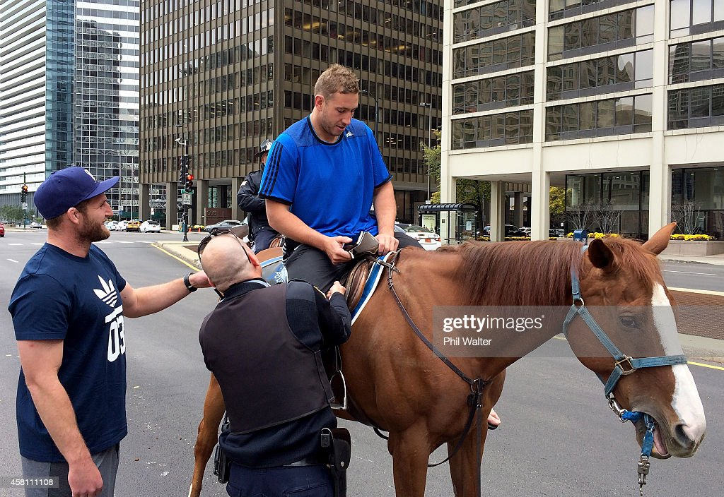 Luke Romanos of the New Zealand All Blacks sits on a horse from the Chicago Police Department Mounted Patrol Unit watched by Kieran Read on October...