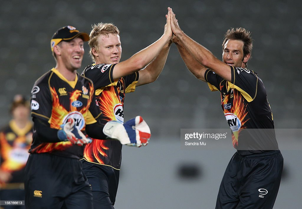 Luke Ronchi, Scott Kuggeleijn and <a gi-track='captionPersonalityLinkClicked' href=/galleries/search?phrase=Grant+Elliott&family=editorial&specificpeople=708027 ng-click='$event.stopPropagation()'>Grant Elliott</a> of Wellington celebrate the wicket of Colin de Grandhomme of Auckland during the HRV Cup Twenty20 match between the Auckland Aces and Wellington Firebirds at Eden Park on December 28, 2012 in Auckland, New Zealand.