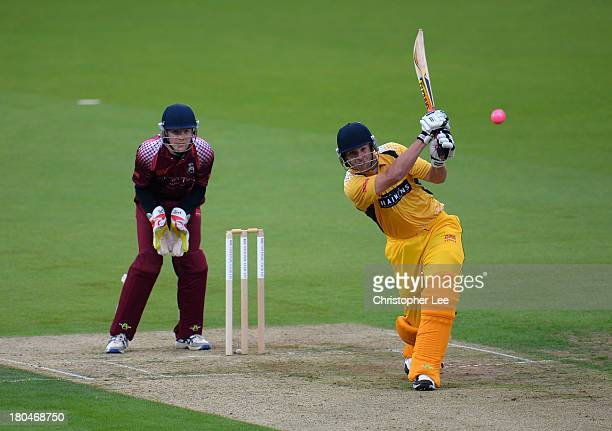 Luke Ryan of Banbury smashes the ball away as wicket keeper James Brown of Wimbledon watches during the Semi Final match between Wimbledon and...