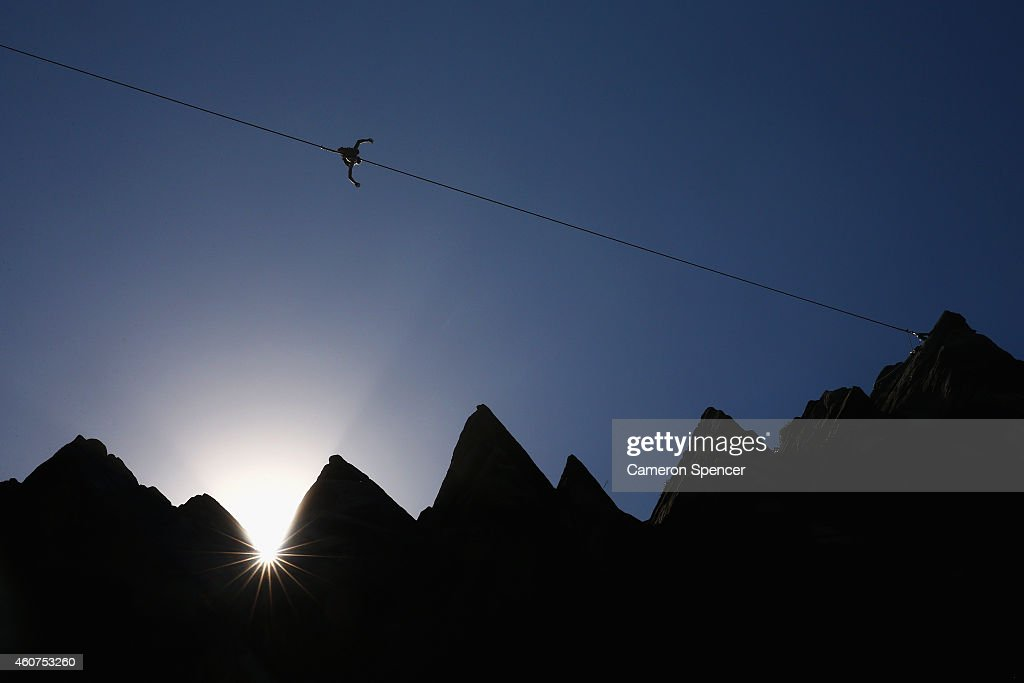 Luke Sarantos walks on a slackline as he highlines between two cliffs at Diamond Bay on December 21, 2014 in Sydney, Australia. Slacklining is a balance sport in which participants walk on a flat nylon webbing anchored between two points with the tension adjusted to allow for slack, providing an experience similar to that of walking on a trampoline. Highlining is a style of slacklining where the two anchor points are set up with significant elevation from the ground or water.