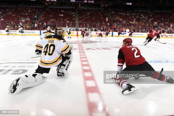 Luke Schenn of the Arizona Coyotes talks with Tuukka Rask of the Boston Bruins during the pregame skate at Gila River Arena on October 14 2017 in...