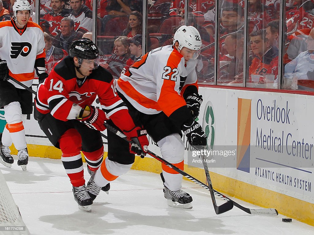 Luke Schenn #22 of the Philadelphia Flyers and Adam Henrique #14 of the New Jersey Devils battle for a loose puck during the game at the Prudential Center on February 15, 2013 in Newark, New Jersey.