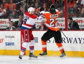 Luke Schenn of the Philadelphia Flyers battles against John Erskine of the Washington Capitals on December 17 2013 at the Wells Fargo Center in...