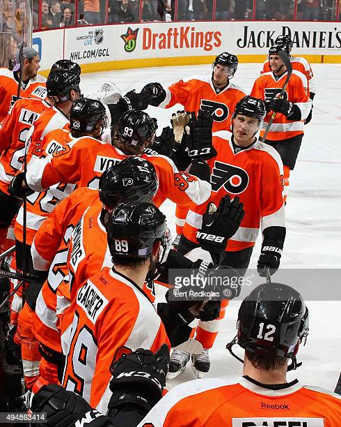 Luke Schenn of the Philadelphia Flyers celebrates his second period goal against the New Jersey Devils with his teammates on the bench on October 29...