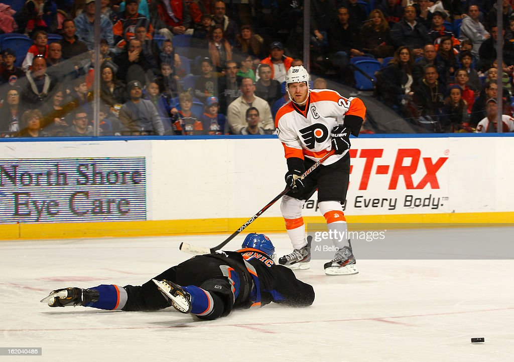 Luke Schenn #22 of the Philadelphia Flyers chases the puck as Travis Hamonic #3 of the New York Islanders dives during their game at Nassau Veterans Memorial Coliseum on February 18, 2013 in Uniondale, New York.