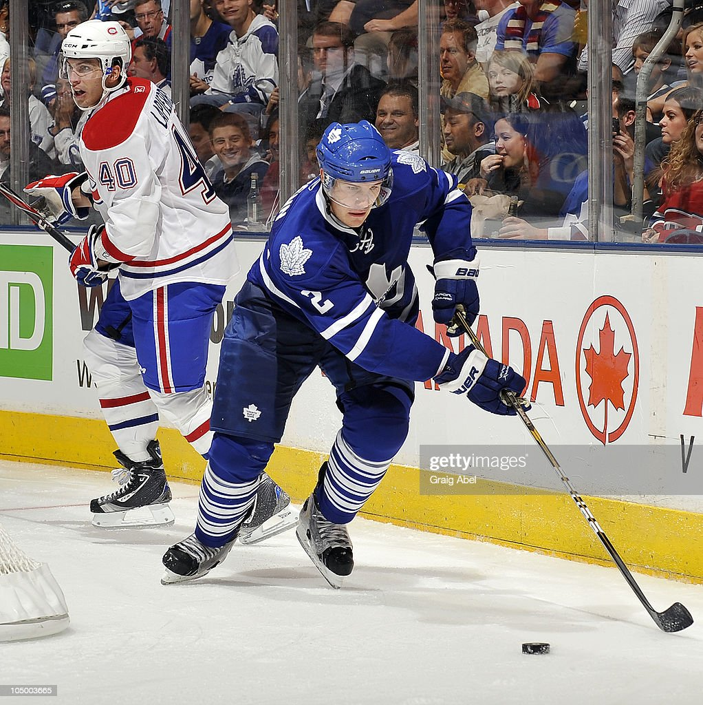 <a gi-track='captionPersonalityLinkClicked' href=/galleries/search?phrase=Luke+Schenn&family=editorial&specificpeople=4254202 ng-click='$event.stopPropagation()'>Luke Schenn</a> #2 of the Toronto Maple Leafs skates the puck away from <a gi-track='captionPersonalityLinkClicked' href=/galleries/search?phrase=Maxim+Lapierre&family=editorial&specificpeople=718385 ng-click='$event.stopPropagation()'>Maxim Lapierre</a> #40 of the Montreal Canadiens during game action October 7, 2010 at the Air Canada Centre in Toronto, Ontario, Canada.