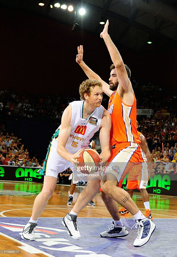 Luke Schenscher of the Crocodiles drives past Ian Crosswhite of the Taipans during the round 25 NBL match between the Cairns Taipans and the...