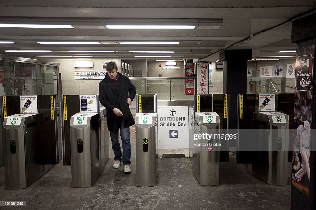 Luke Schiefelbein, an MIT student, pays at the turnstile at the start of T service as T riders wait for service to start on the green line at Kenmore Square in Boston, Mass. on Sunday, February 10, 2013. The MBTA announced it would resume limited service at 2 p.m.