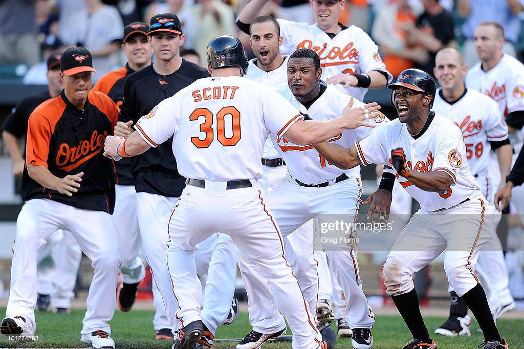 Luke Scott of the Baltimore Orioles is congratulated by Adam Jones Corey Patterson Nick Markakis and other teammates after scoring the game winning...