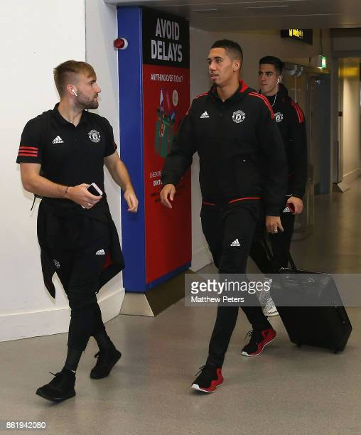Luke Shaw and Chris Smalling of Manchester United checks in ahead of their flight to Lisbon for the UEFA Champions League match against Benfica at...