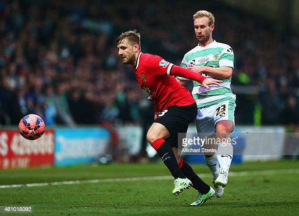 Luke Shaw of Manchester United holds off Simon Gillett of Yeovil Town during the FA Cup Third Round match between Yeovil Town and Manchester United...