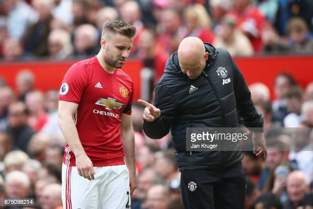 Luke Shaw of Manchester United speaks to Carlos Lalin Manchester United coach after he is forced off with a injury during the Premier League match...