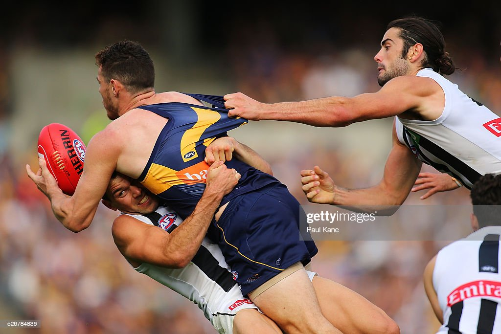 Luke Shuey of the Eagles gets taclked by Levi Greenwood and Brodie Grundy of the Magpies during the round six AFL match between the West Coast Eagles and the Collingwood Magpies at Domain Stadium on May 1, 2016 in Perth, Australia.